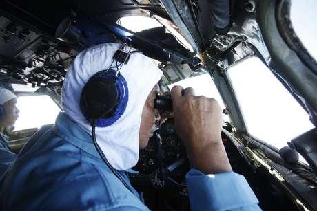 Militar vietnamita usa binóculos para tentar encontrar o avião desaparecido