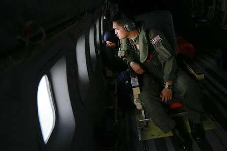 <p>Membroda Força Aérea da Malásiaolhapelajanelade um avião da durante operação de busca para encontrar o aviãodesaparecido daMalaysia Airlines, no Estreito de Malaca, nesta quinta-feira, 13 de março</p>