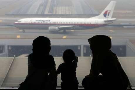 <p>Segundo autoridades, as fotos dos supostos destroços do avião desaparecido foram divulgadas por engano e não mostram de fato pedaços da aeronave. Na foto, passageiros da Malaysian Airlines aguardam voo da companhia aérea no aeroporto de Kuala Lumpur, em 13 de março</p>