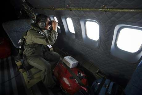 Un socorrista observa con binoculares durante la búsqueda del vuelo MH370 de Malaysia Airlines en el estrecho de Malacca, Indonesia, mar 14 2014. La investigación sobre la desaparición de un avión de Malaysia Airlines se centra cada vez más en la sospecha de que el vuelo fue desviado deliberadamente, ya que la evidencia sugiere que se dirigía hacia las islas Andamán fuera de su curso, dijeron fuentes familiares con la pesquisa.