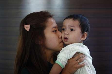 <p>Erny Khairul, mulher do engenheiro de voo Mohd Selamat, a bordo no avião desaparecido beija sua filha em hotel, onde esperam notícias sobre avião em Putrajaya</p>