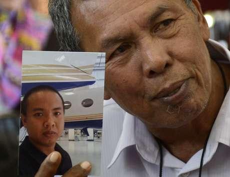 <p>O pai de Mohd Selamat mostra a foto do filho que estava a bordo do avião desaparecido. A polícia do país investiga possível participação do engenheiro na mudança de rota do Boeing</p>