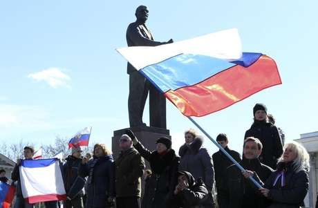 Participantes de uma manifestação pró-Rússia agitam bandeiras russas na frente da estátua de Lenin, em Simferopol. Os ministros das Relações Exteriores da União Europeia concordaram em impor sanções contra 21 pessoas da Rússia e da Ucrânia nesta segunda-feira, incluindo proibições de viagens e congelamento de bens, disse o chanceler da Lituânia nesta segunda-feira. 17/03/2014