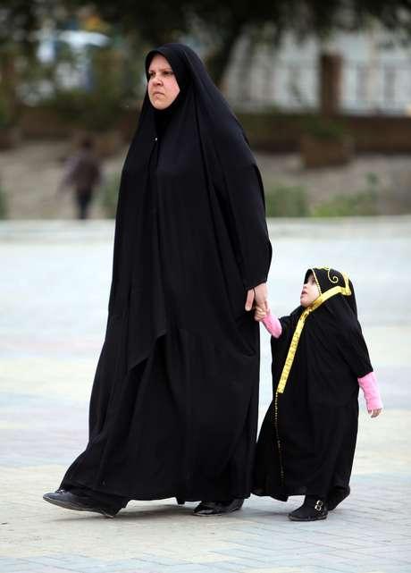 Mulher iraquiana anda com sua filha em Bagdá, nesta terça-feira, 18 de março, enquanto país discute casamento infantil