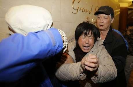 <p>Familiares de passageiros do voo da Malaysian Airlines choram ao saber que avião caiu no Índico</p>