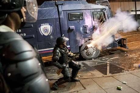 Agentes da Guarda Nacional Bolivariana enfrentam grupos de manifestantes em Caracas, em 3 de abril