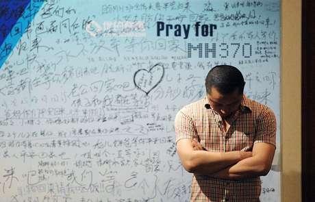 <p>Familiar cruza os braços em frente a um painel que homenageia passageiros do voo MH370</p>