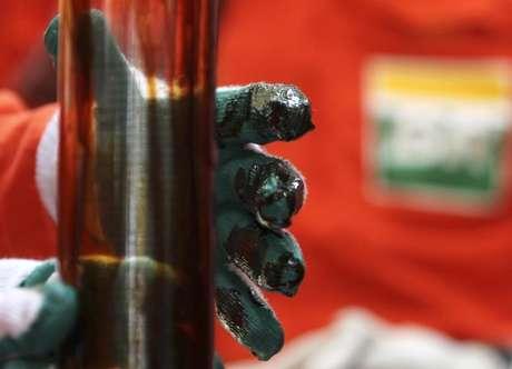 Operário checa amostra de óleo na plataforma de petróleo Cidade Angra dos Reis, no campo de Lula, Rio de Janeiro. A produção da Petrobras no Brasil e exterior somou 2,55 milhões de barris/dia de óleo equivalente em março, alta de 0,63 por cento ante o mês anterior e de 2,6 por cento na comparação com o volume extraído um ano antes, informou a empresa nesta quarta-feira. 16/02/2011.