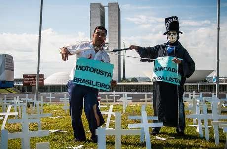 Manifestantes utilizam cruzes, fantasias e cartazes durante protesto
