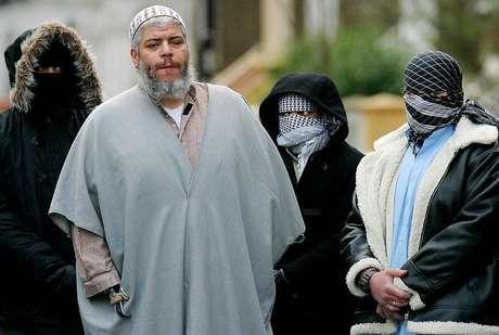 <p>Fotografia de 2003 mostra o clérigo muçulmano Abu Hamza fora da mesquita, em Londres, cercado por apoiadores</p>