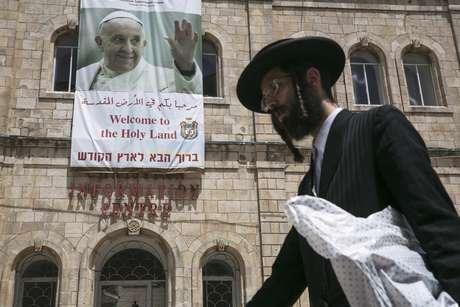 <p>Judeu ultra-ortodoxo é visto passando em frente de um cartaz em homenagem ao Papa, na Velha Jerusalém</p>