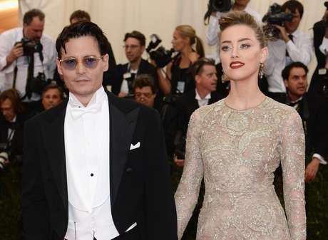 Ao lado do namorado Johnny Deep, no Festival de Cannes 2014, Amber Heard brilha com batom vermelho-escuro e brilho nos olhos, como do vestido