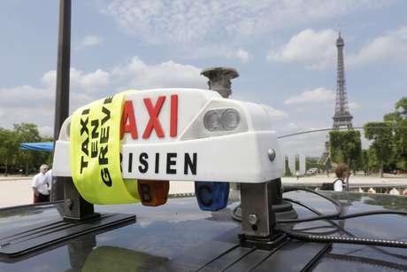 <p>Fitas amarelas colocadas nos veículossinalizam a participação em uma manifestação de taxistas perto da Torre Eiffel, em Paris, nesta quarta-feira, 11 de junho</p>