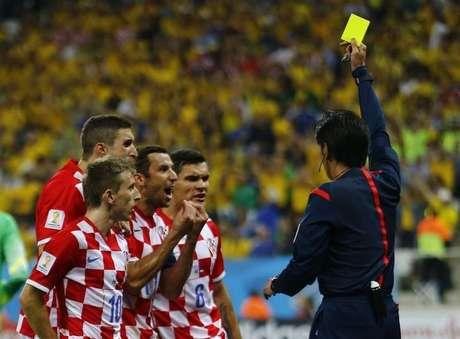 Juiz Yuichi Nishimura mostra cartão amarelho para jogador croata após marcar pênalti a favor do Brasil, na partida inicial da Copa do Mundo, em São Paulo. 12/6/2014