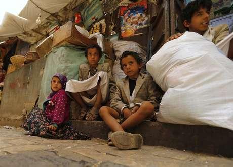 <p>Crian&ccedil;as sentadas&nbsp;em um mercado na cidade velha de Sanaa, no I&ecirc;men, em 17 de junho</p>