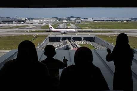 <p>Pessoas olham para fora de uma janela enquanto um Boeing da Malaysia Airlines taxia no Aeroporto Internacional de Kuala Lumpur, na Malásia, em14 de junho</p>