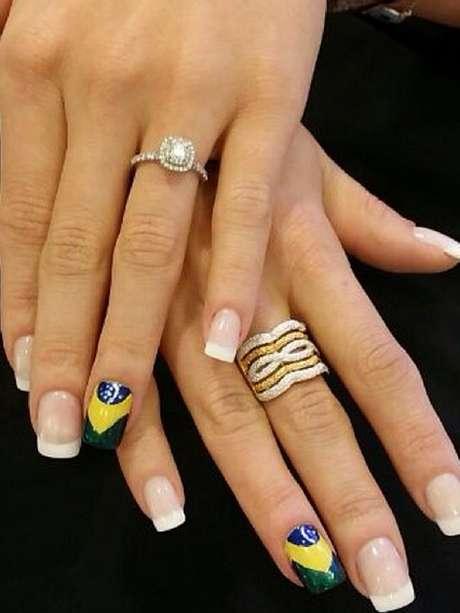 <p>Opção mais delicada, também postada por Biaggi, mostra unhas brancas no estilo francesinha e filha única com a bandeira do Brasil. Trabalho da celebrada manicure de seu salão, Eliane Sampaio</p>