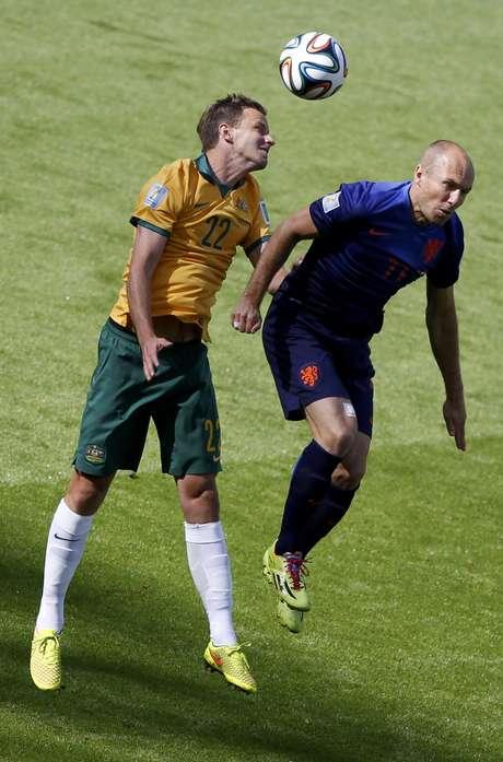 <p>Alex Wilkinson e Robben disputam bola aérea durante jogo entre Austália e Holanda, no Estádio Beira Rio, em Porto Alegre</p>
