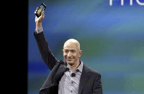 """En la imagen, el CEO de Amazon, Jeff Bezos, muestra el nuevo móvil de su empresa: el Fire Phone, en una rueda de prensa en Seattle, Washington, el 18 de junio de 2014.   Bezos presentó el miércoles el teléfono inteligente """"Fire"""", que posee almacenamiento gratuito e ilimitado de fotografías, en su entrada a un concurrido campo dominado por Apple Inc y Samsung Electronics."""