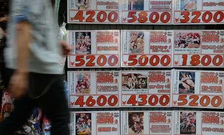 <p>Um homem caminha próximo a uma loja de de DVDs de segunda mão que exibe propaganda de vídeos pornográficos, em Tóquio, Japão, em 4 de junho</p>