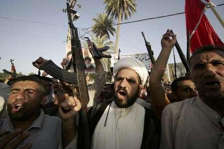 <p>Combatentes tribais carregam armas durante uma marcha em Kerbala, no sul de Bagdá, no Iraque</p>