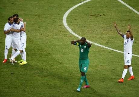 Yaya Toure, da Costa do Marfim, lamenta, enquanto jogadores da Grécia comemoram após partida em Fortaleza. 24/06/2014.