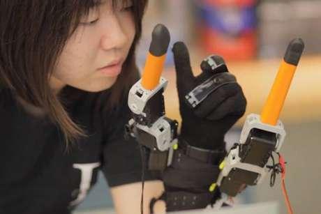<p>Estudante do MIT demonstra o dispositivo, que é usado como uma luva, e tem os dedos artificiais próximos ao polegar e ao mindinho</p>
