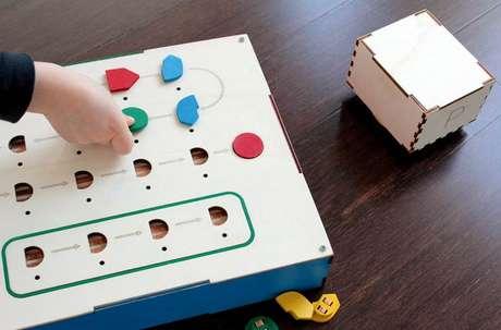 <p>Primo é composto de três partes: um robô em forma de cubo (à direita), uma interface de controle e botões de comando. Estes devem ser inseridos na interface para criar a sequência de movimentos do robô</p>