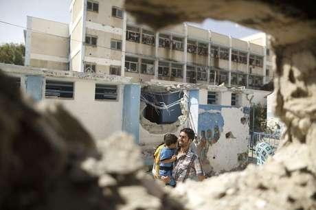 <p>Homem passa por escola da ONU em Gaza que, segundo testemunhas, foi alvo de ataque de Israel</p>
