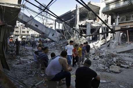 <p>Palestinos observam os destro&ccedil;os da torre de uma mesquita que, segundo policiais, foi destru&iacute;da por ataque a&eacute;reo israelense, na Faixa de Gaza, nesta quarta-feira</p>