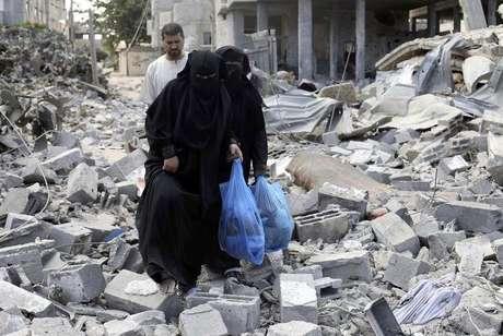 <p>Palestinas caminham sobre destro&ccedil;os de casa em Rafah que, segundo testemunhas, foram destru&iacute;das por ataque de Israel</p>