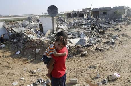 Menino palestino carrega o irmão no colo em frente aos destroços da casa da família em Gaza, em 13 de agosto