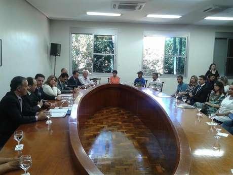 <p>Em reunião com os parentes das vítimas, o governador Marconi Perillo observa o secretário de Segurança Pública discursar para o grupo</p>