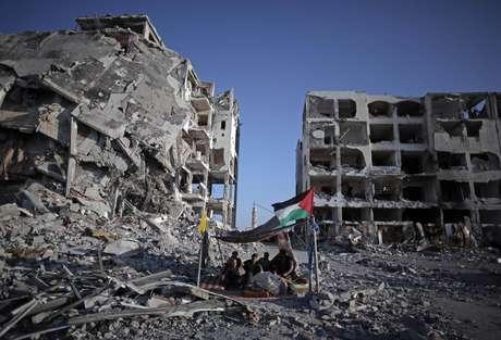 <p>Palestinos que perderam suascasas e seus estabelecimentos durante a ofensiva israelense sentam-se em um abrigo improvisadona cidade de Beit Lahiya, norte da Faixa de Gaza, em 11 de agosto</p>
