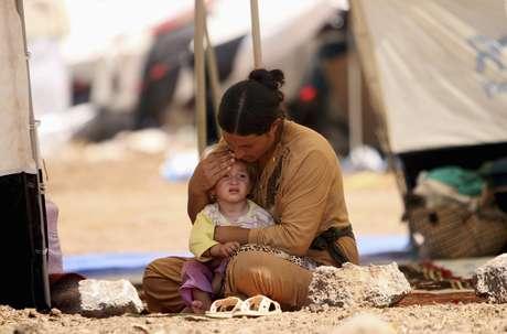 Mulher e criança da minoria yazidi, do Iraque, se refugiam em campo na Síria