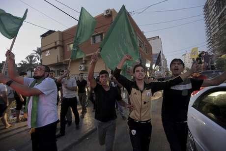 <p>Palestinos brandem&nbsp;bandeiras nacionais durante celebra&ccedil;&atilde;o do acordo de cessar-fogo entre Israel e Hamas&nbsp;na principal rua da Cidade de Gaza</p>