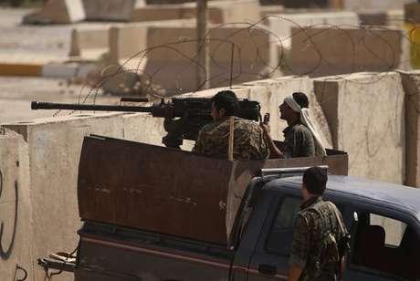 <p>Tropas curdas tomam&nbsp;posi&ccedil;&atilde;o atr&aacute;s de blocos de cimento na cidade iraquiana de Rabia, na fronteira do Iraque com a&nbsp;S&iacute;ria, durante confrontos com militantes do Estado Isl&acirc;mico, em 29 de agosto</p>