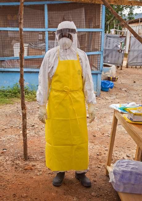 Agente de saúde veste roupa para entrar em centro de tratamento em Serra Leoa
