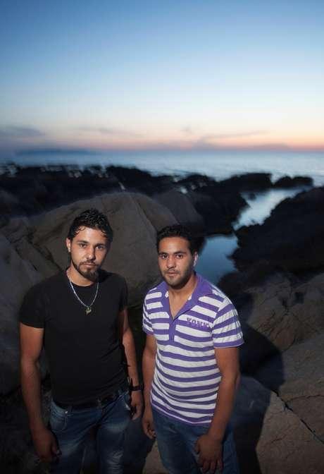<p>Os irmãos e refugiados sírios Thamer e Thayer posam em frente à costa no oeste da Sicília</p>