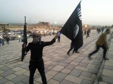 <p>Um integrante do Estado Isl&acirc;mico exibe&nbsp;uma bandeira do grupo terrorista em uma rua da cidade de Mossul, em 23 de junho</p>