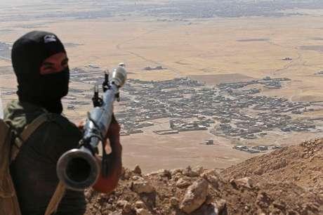 Combatente  curdo peshmerga com lançador de granada apontado para o vilarejo de Baretle, que é controlado pelo Estado Islâmico, no Iraque.