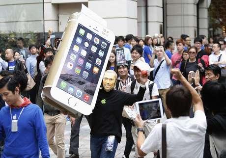 """No Japão, humor deu o tom da fila de espera; homem com máscara do Steve Jobs passeia com um iPhone 6 """"gigante"""" de papelão nas ruas de Tóquio"""