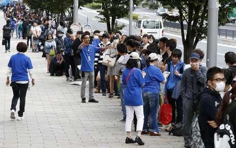 Funcionários da Apple tentam organizar a fila em frente a loja da Apple em Tóquio, Japão