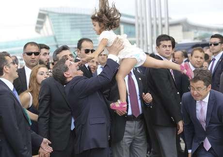 <p>O primeiro-ministro turco, Ahmet Davutoglu(ao centro), joga para o alto afilha doCônsul Geral da Turquia em Mossul,Ozturk Yilmaz, ao comemorar a chegada dos reféns do Estado Islâmico</p><p></p>