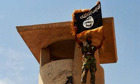 <p>Membro do Estado Isl&acirc;mico exibe bandeira do grupo terrorista em territ&oacute;rio conquistado no Iraque</p>