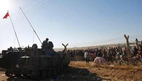 Curdos sírios aguardam na fronteira diante de soldados turcos nesta segunda-feira. Milhares deles têm fugido devido ao avanço do Estado Islâmico.