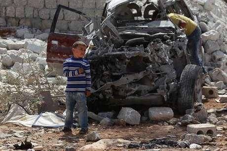 <p>Meninos observam carro destruído por ataque aéreo de terça-feira dos EUA em Kfredrian, na Síria, segundo ativistas</p>