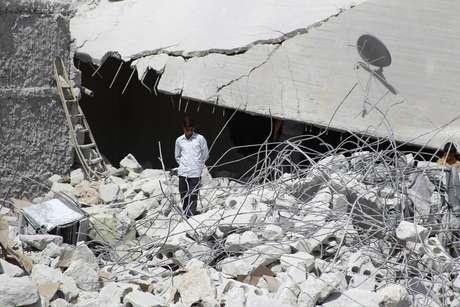 Menino anda entre escombros de prédio destruído durante ataques desta terça-feira