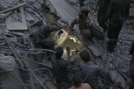 Sobreviventes procuram por desaparecidos após os bombardeios aéreos pelo exército sírio