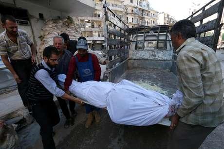 Homens carregam corpo de um morto durante conflitos em Aleppo